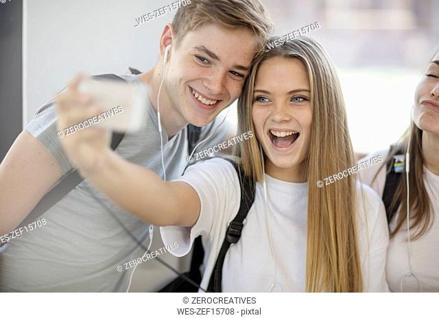 Happy students taking a selfie in school