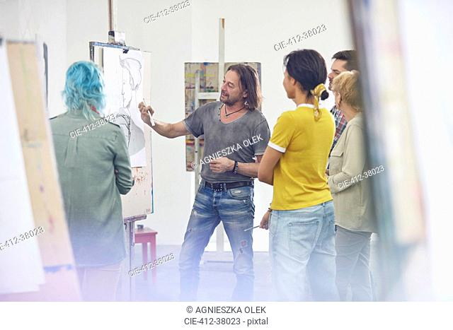 Students listening to instructor sketching at easel in art class studio