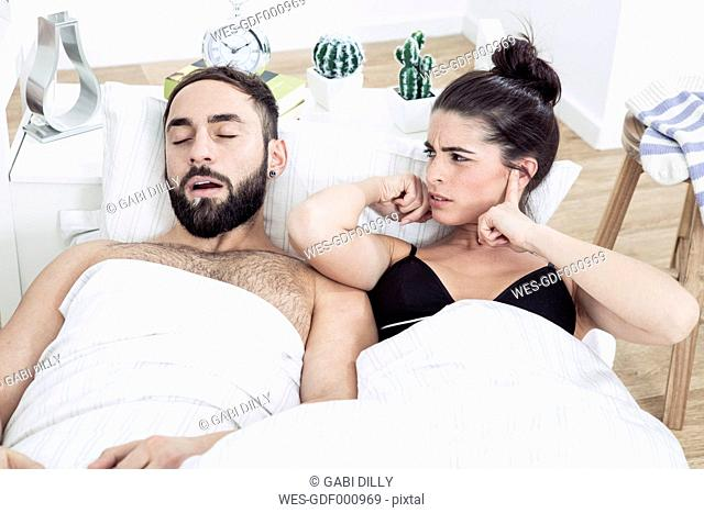 Couple lying in bed with man snoring