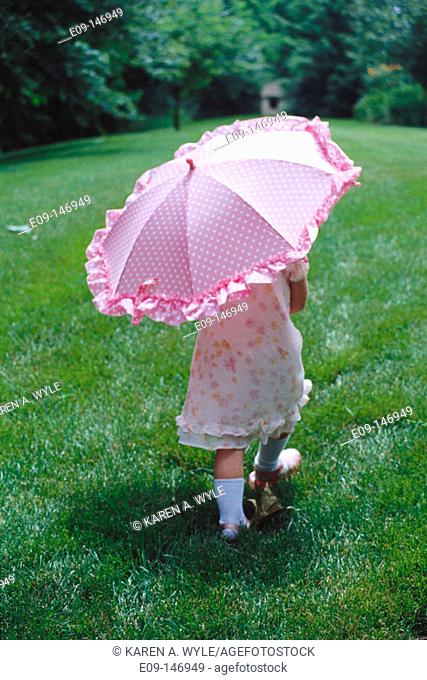 Small girl walking, holding a pink umbrella, viewed from behind