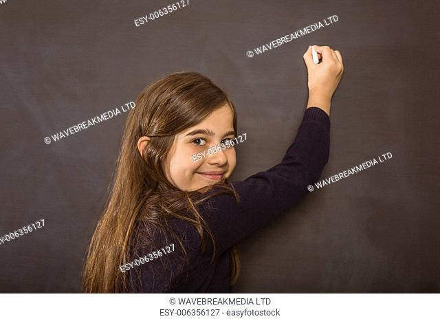 Cute pupil writing on chalkboard on black background