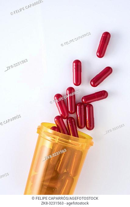 capsules going out of a bottle, conceptual image, vertical composition