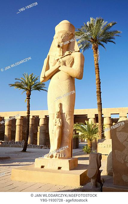 Karnak, Egypt - Statue of Pharaoh Ramses II with Queen Nefertari in the Great Courtyard, Amun-Re Temple, Karnak temple complex, Upper Egypt, UNESCO