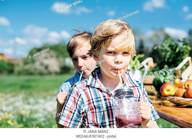 Two boys outdoors drinking from jars
