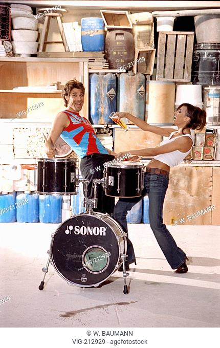 Couple behind a drumkit. The woman wants to pure beer in the man's trousers.  - x, 30/12/2005