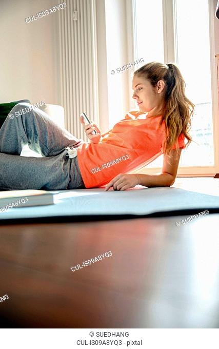 Young woman using smartphone whilst lounging on floor