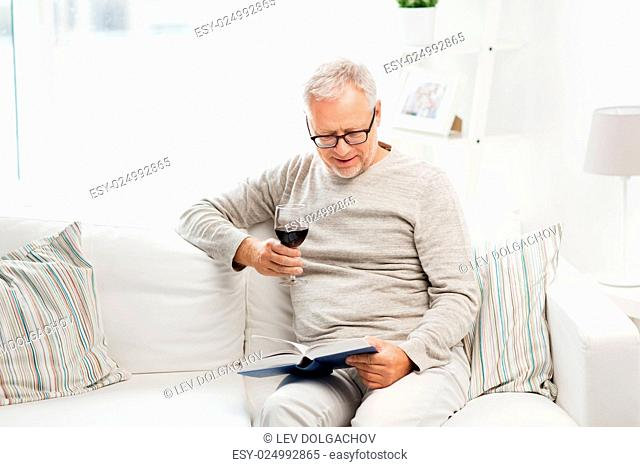 age, leisure and people concept - happy smiling senior man with wine glass reading book at home
