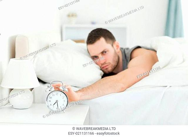 Man being awakened by an alarm clock