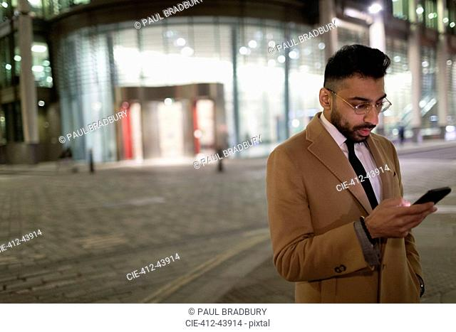 Businessman texting with smart phone on urban street corner at night