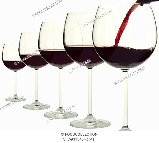 Five red wine glasses in a row