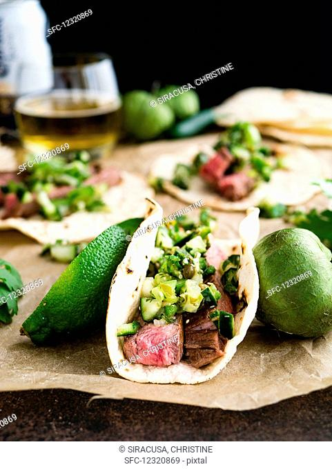 Tacos with flank steak, Pico de Gallo Verde, limes and tomatoes