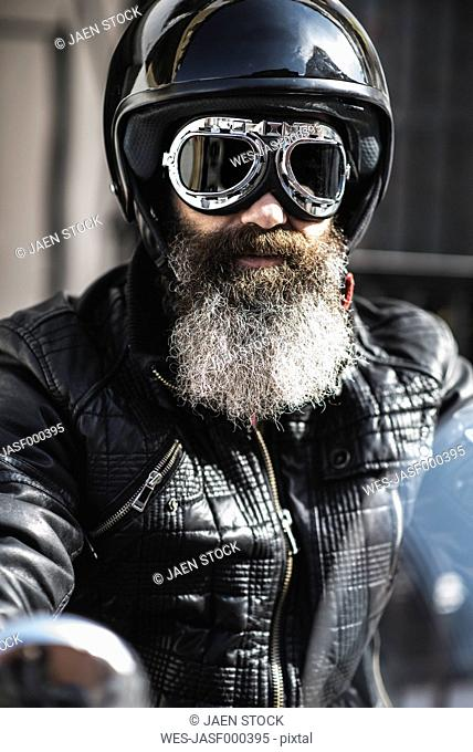 Portrait of bearded biker wearing black leather jacket, helmet and goggles
