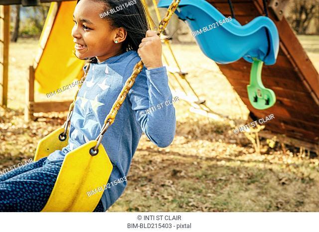 Black girl sitting on swing set