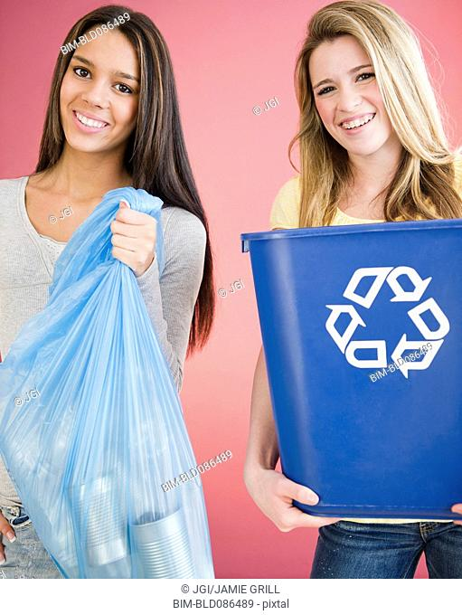Teenage girls carrying recycling