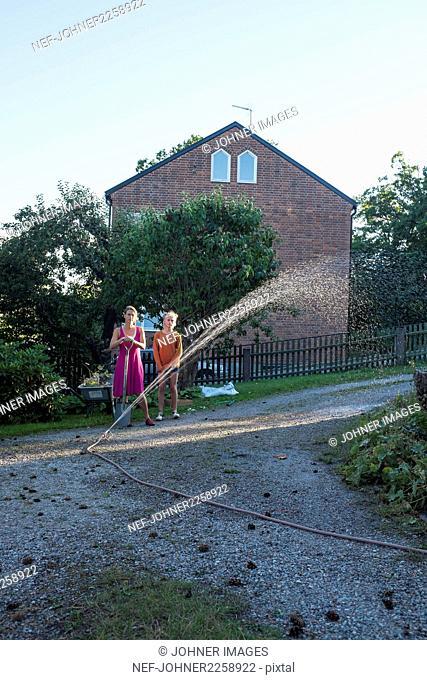 Mother with daughter watering garden
