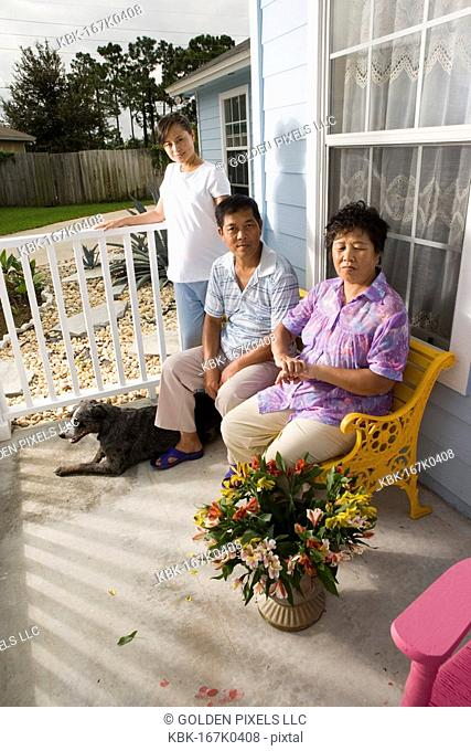 Portrait of pregnant woman with her parents seated in front porch of house