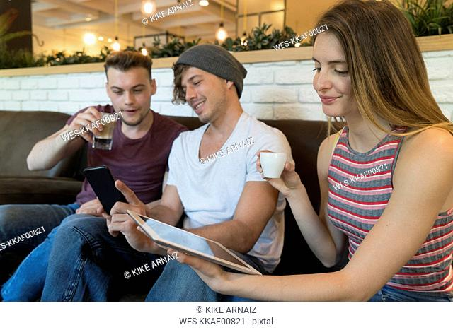 Three friends using tablet and cell phone in a cafe