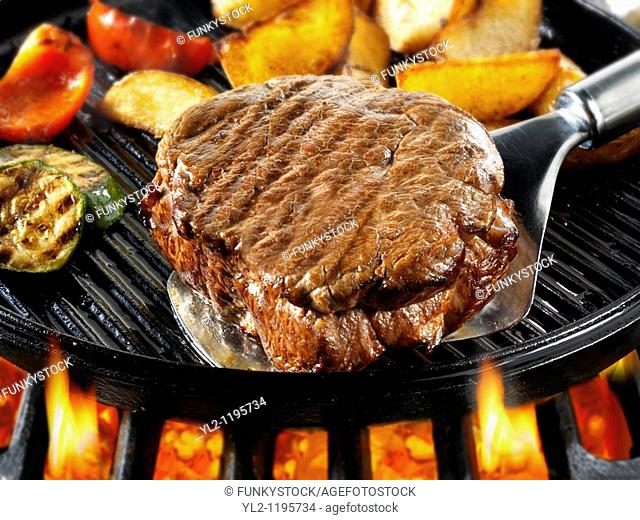 Beef fillet steaks, chips & roast peppers being pan fried on a bbq