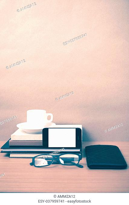 coffee,phone,eyeglasses,stack of book and wallet on wood table background vintage style