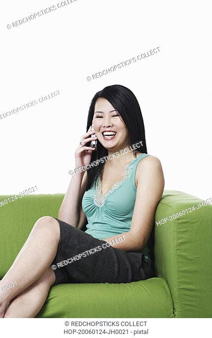 Portrait of a young woman sitting on a couch talking on a mobile phone