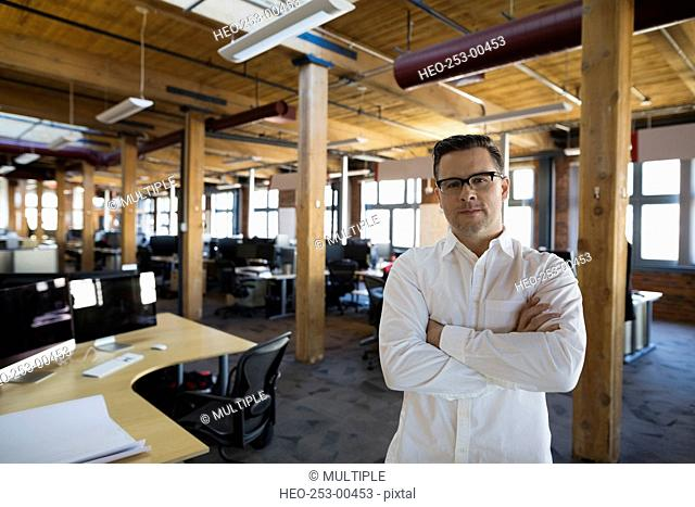 Portrait confident businessman arms crossed in open office