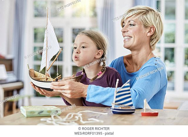 Happy mother and daughter playing with model boat at home