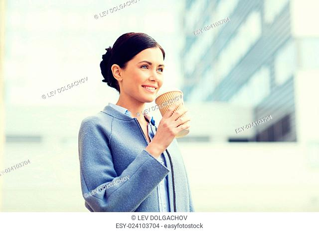 business, drinks, leisure and people concept - smiling woman drinking coffee over office building in city