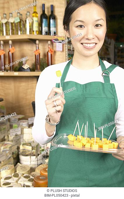 Asian female supermarket worker with cheese samples