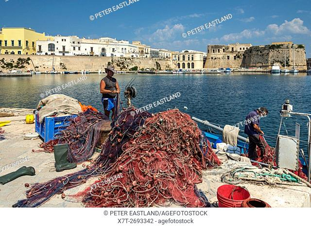 Fishermen mending fishing nets and cleaning boats at the quay in the old town of Gallipoli, Puglia, Southern Italy