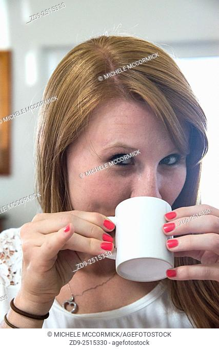 A young woman sips her coffee