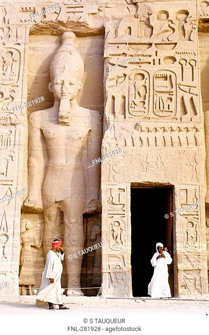 Two people in front of Egyptian temple, Nefertaris Temple Of Hathor, Abu Simbel, Egypt