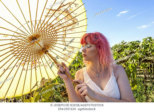 A 25 year old woman with pink hair, in a field of drying sunflowers holding a parasol looking away from the camera, the Alabama USA