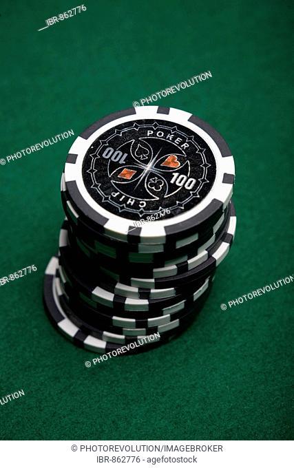 Stacked black poker chips on green felt