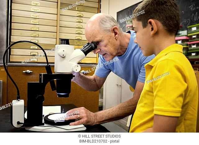 Teacher and student using microscope in laboratory