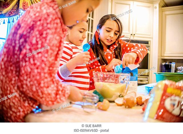 Children in kitchen wearing pyjamas baking