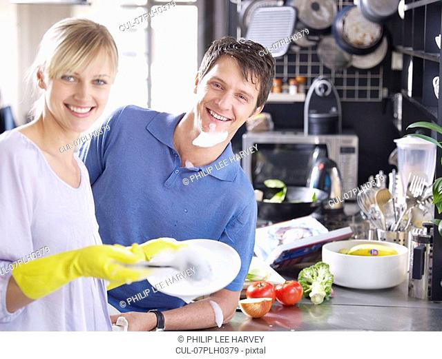 Woman and man in kitchen washing up