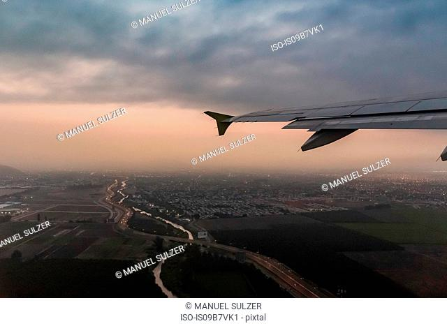 Airplane wing and aerial view of Punta Arenas city lights at dusk, Magallanes Region, Chile