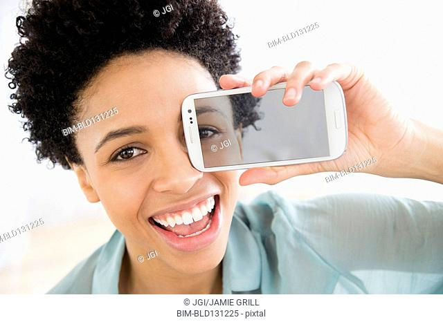 Black woman holding photo of her eye over her face