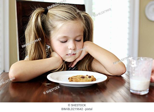 Girl staring at cookie with milk at table