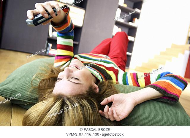 Young woman lying on a cushion holding a mobile phone