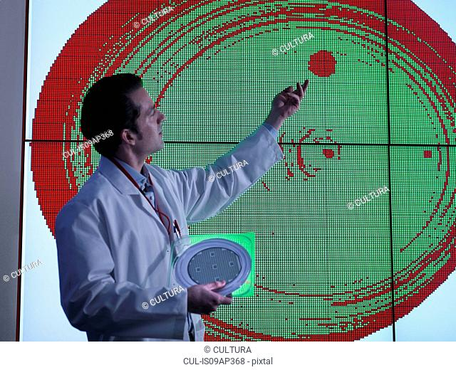Scientist studying graphical display of silicon wafer on screens