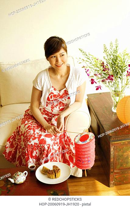 High angle view of a young woman sitting on a couch and holding a Chinese lantern