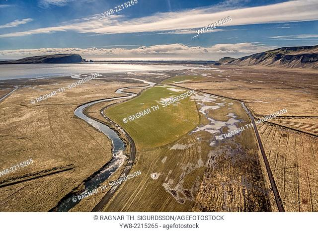 Aerial view of rivers and farmland with Dyrholaey and Reynisdranger cliffs in the background, South Coast, Iceland