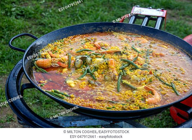 A large pan of seafood paella being prepared outdoors