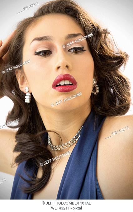 Beautiful young woman head and shoulders portrait in vintage blue dress, with a dreamy, glamorous look and eyes turned aside, chin up