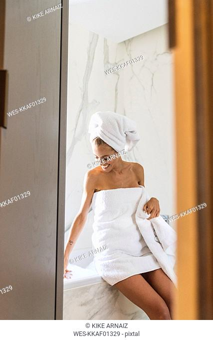 Woman wrapped in towels, sitting on edge of bathtub