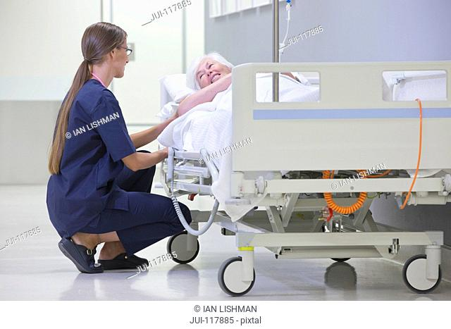 Nurse Talking To Patient On Gurney In Hospital Corridor