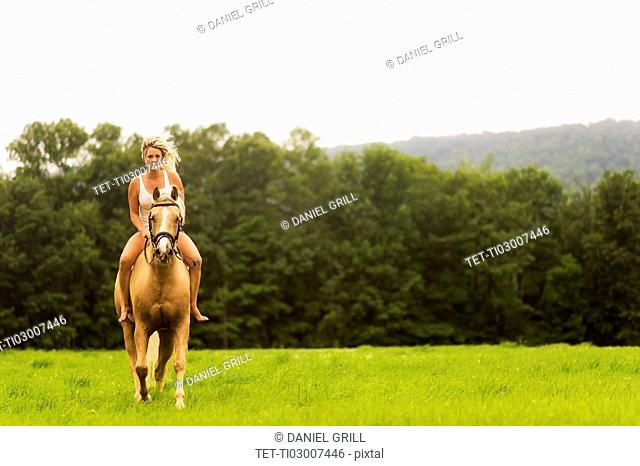 Woman horseback riding in countryside