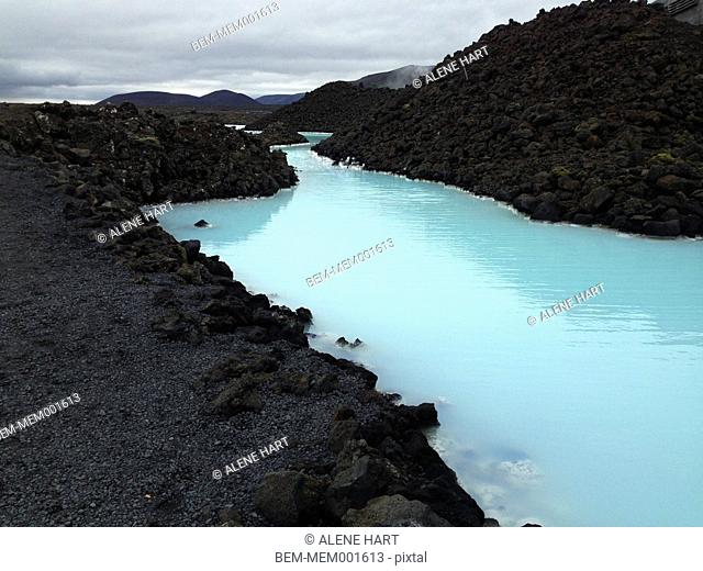 Sulfurous geothermal lake in rocky volcanic landscape