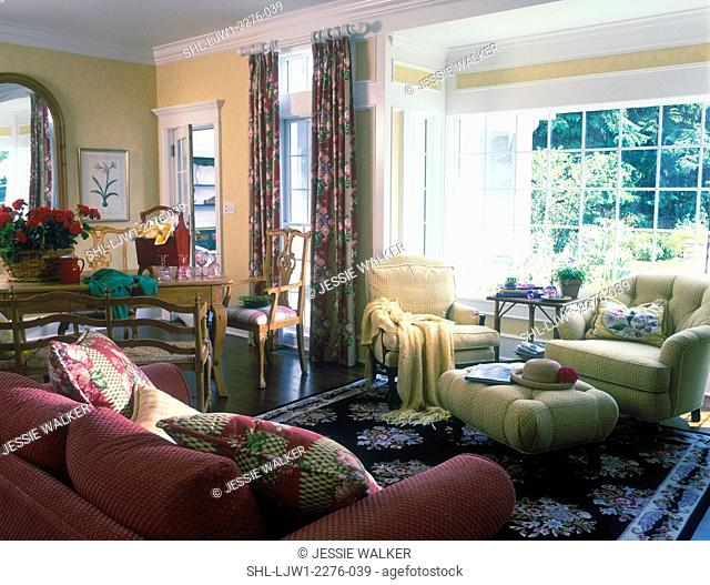 FAMILY SITTING AREA - Bay window, yeloow walls, white trim, black area rug, yellow upholstered armchairs and ottoman, backside of paprika sofa
